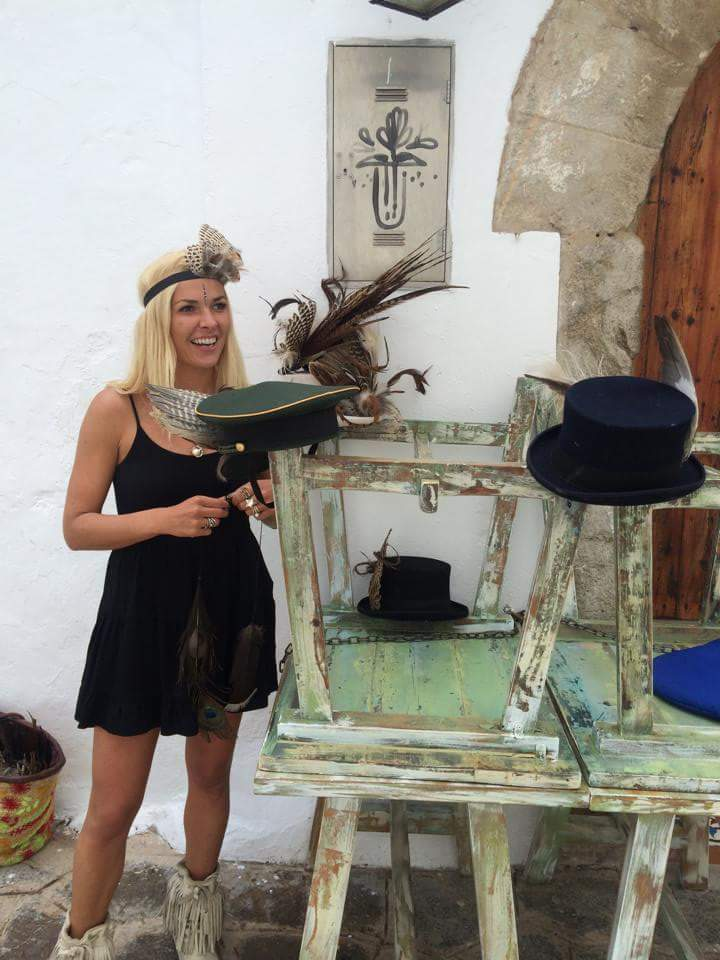 A blond lady smiling in front of some hats and feathered headdresses.